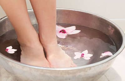 feet in bowl of water with flowers